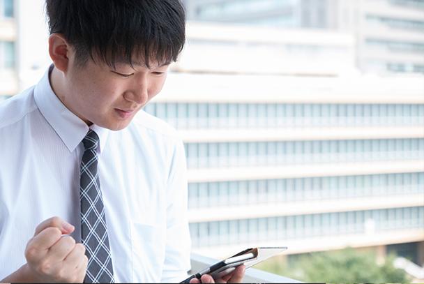 スマートフォンで仕事をする笑顔の男性社員